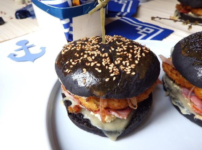 Burger breton recette terre et mer avec des buns à l'encre de sèche, lard, poisson pané, et mayonnaise façon sauce au beurre blanc