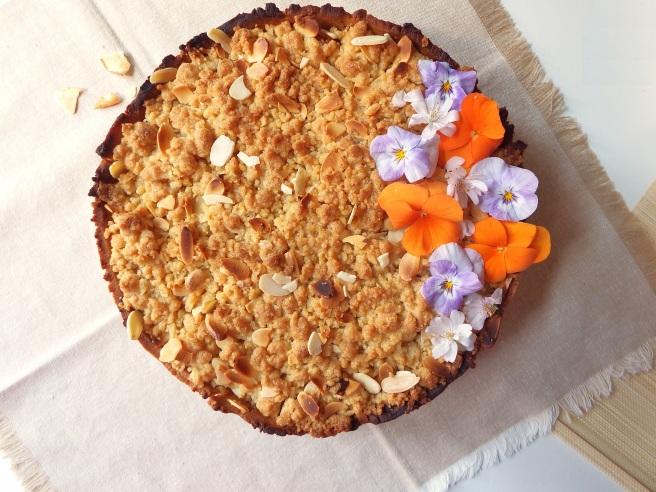 Crumble aux pommes et au chocolat dans une pâte sablée aux spéculoos avec des fleurs de pensées